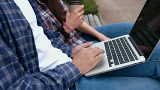 Young urban people in checkered shirts and blue jeans using computer laptop and drinking coffee from to go cup on bench