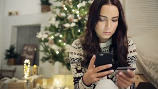 Young woman buying gifts with credit card on Christmas at home