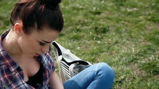 Young woman in casual clothes writing in her journal sitting on grass in the park, close-up