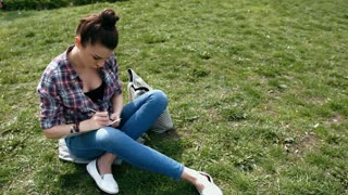 Young woman in casual clothes writing in her journal sitting on grass in the park