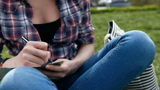 Young woman in in checkered shirt and blue jeans writing in her journal sitting on grass in the park, close-up