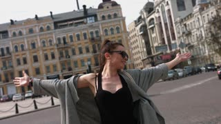 Young woman spreading hands wide open with city on background. Freedom concept