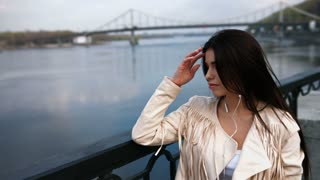 Young woman standing on the modern bridge, river on background, touching her hair, listening to music with headphones