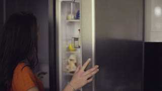 Young woman taking out fruit from the fridge. Healthy Eating Concept. Diet. Beautiful Young Woman near the Refrigerator with healthy food. Fruits and Vegetables in a Fridge