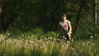 Girl runs on dandelion grass