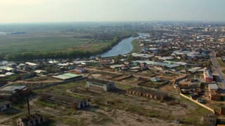 Aerial view of industrial buildings in city from helicopter. Flying above city on drone. Flying above countryside with river on drone in Russia