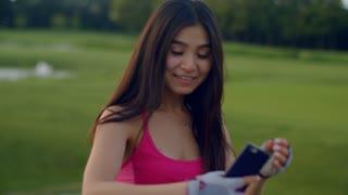 Asian girl taking selfie in park. Sport girl selfie on phone in park. Attractive girl selfie photo. Fit girl smiling and taking selfi. Smiling woman using phone to make selfie portrait on meadow