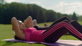 Asian woman doing sit ups in spring park. Closeup of fitness woman doing sit up exercise at sunny day. Outdoor fitness workout. Fit girl doing crunch exercise. Physical training for abdominal muscle