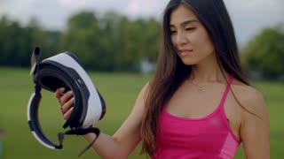 Asian woman examine vr headset outdoor. Sport girl looking at vr glasses in park. Close up of woman holding vr device in hands. Young woman exploring virtual reality glasses. Woman vr headset