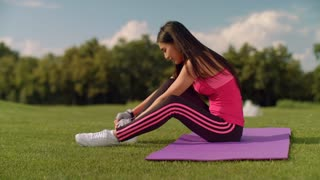 Asian woman in sports wear preparing for fitness workout outdoor. Fitness woman sitting on yoga mat at green grass. Sporty woman preparing for fitness training. Chinese woman prepare for yoga training