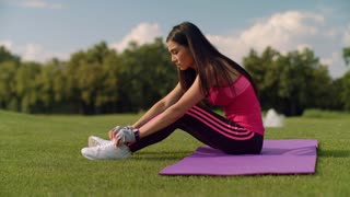 Asian woman sitting on mat and tying shoelaces in summer park. Fitness woman preparing for fitness training. Asian girl tying laces on her running sneakers.