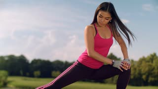 Asian woman stretching legs outdoor. Fitness woman doing stretching exercise for legs before fitness workout. Closeup of asian runner stretching legs before running in park