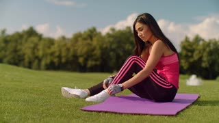 Asian woman tying laces on her sneakers. Cute girl stretching on yoga mat and tying shoelaces in summer park. Sportswoman preparing for fitness training. Fit girl warming up arms before training