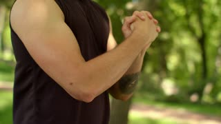 Athletic man stretching hands. Guy warm up wrist in park. Fit boy training outdoor. Close up of sport man doing fitness exercise close up. Tattoo on hand sporty man doing stretching exercise