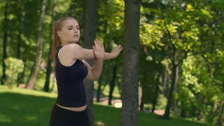 Attractive female runner stretching in summer park. Fit girl doing stretching exercise outdoors. Fitness trainer stretching arm. Woman warm up before running. Healthy lifestyle and fitness workout
