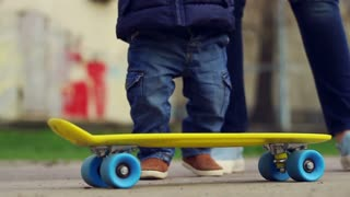 Baby on skateboard. Child legs ride on skate in outdoor. Baby feet skateboarding on blue and yellow board. Little child with parent. Nice kid in jeans and brown shoes learn skateboarding