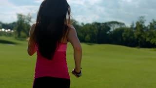Back of woman running in park. Fit girl running in slow motion. Sport woman running exercise. Running woman with long hair. Sporty girl jogging outdoors. Female runner training