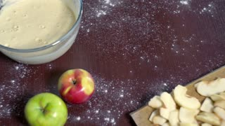 Baking cake. Dough pouring into a round baking dish. Apple pie ingredients. Baking ingredients. Cake batter pouring in baking pan. Chef pours dough in slow motion. Baking utensils. Home baking