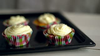 Baking cupcakes. Cupcakes on baking tray. Sweet cupcakes. Sweet food. Tasty cakes with cake cream. Muffins with butter cream. Dessert cake with coconut. Delicious dessert closeup