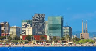 Barcelona beach. Timelapse of Barcelona city beach view. Resort at Spain. Travel destination. Time lapse of mediterranean coast in Barcelona at sunny day. Cloudless sky over buildings at sea beach