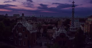Barcelona landmarks. Morning in Park Guell designed by Antoni Gaudi in Barcelona, Spain. Timelapse of clouds over european city at sunrise. View of travel landmarks in Europe. Modern architecture