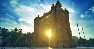 Barcelona landmarks. Sun rays in Triumphal arch in Barcelona, Spain. Sun shine through old gates of Barcelona. Timelapse of tourists walking near city landmark at sunrise. White clouds on blue sky