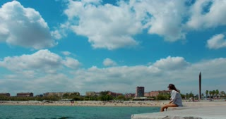 Barcelona, Spain - june 03, 2015: People relax on Barcelona beach. Time lapse of white clouds on sky over blue mediterranean sea. Timelapse. Couple of people at sea resort. Hotel Arts in background