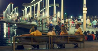 BARCELONA, SPAIN - JUNE 3, 2016: Tourists walks on bridge over Port Vell marina at night. People sitting on banches and dmire views of sea port at night. Illuminated bridge over sea