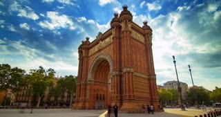 Barcelona triumphal arc. Timelapse of clouds sky over Barcelona triumphal arch. Brick triumphal arch in spain. Travel destination. Famous architecture monument. Barcelona city square