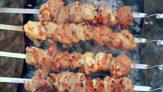 BBQ meat cooking on charcoal. Closeup. Woman tasting piece of meat and turning skewers with meat pieces. People cook delicious kebabs on metal skewers on coals outdoors. Meat with ruddy crust