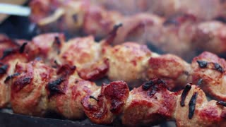 BBQ meat grilling on wood coal. Cooking shish kebab on metal skewers. Tasty grilled meat. Closeup. Man turns skewers with roasted meat. Grilling meat with crust. Grilling shashlik on barbecue grill