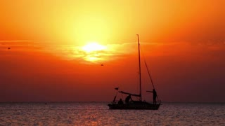 Boat at sunset. Yacht sailing at sea sunset. Sailboat at lake at sunset. Boat sailing at sea sunset. Sailboat silhouette. Birds flying over sea at sunset. Boat at lake sunrise
