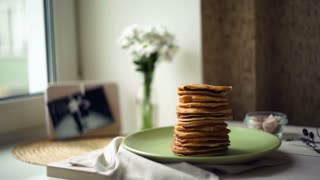 Breakfast for whole family. morning time. breakfast food. pancake day. delicious pancakes on green plate on kitchen table. man hand takes pancakes from stack one at time, until last