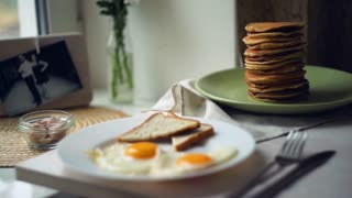 Breakfast plate. Fried eggs with bread toasts and pancake stack on plates on kitchen table. Close up of traditional american meals for breakfast. Traditional dishes for morning breakfast