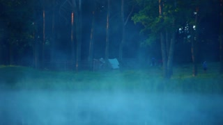 Camping under the pine forest. Camping tents on riverbank. Morning mist over forest lake. Tourists in forest. Fog over forest river. Mist over forest lake. Tourist camp in forest on riverbank