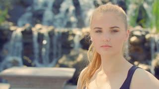 Caucasian woman at nature. Blonde woman portrait outdoor. Woman face. Young woman near waterfall. Serious woman portrait. Blonde girl. Woman posing. Attractive woman. Teenage girl. Thoughtful woman