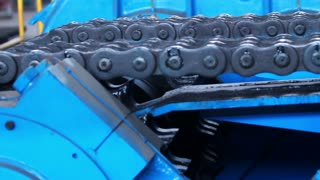 Chain gear. Machine with chain transmission at the factory. Closeup of machinery part. Industrial equipment. Metal chain and sprocket. Steel chain