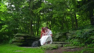 Cheerful couple resting on stone near waterfall in forest. Love couple kissing near waterfall. Romantic couple relaxing at nature. Young people hugging and kissing in park. Romantic relationship