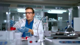 Chemist studying liquid in glass flask at modern lab. Laboratory worker finding a cure. Scientist working at research laboratory. Doctor doing medical research at science lab. Chemistry lab