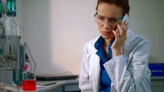 Chemist woman speaking on the phone. Female chemist in lab. Chemistry woman talking on phone in chemistry lab. Chemistry scientist discussion. Mobile conversation in chemical lab