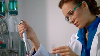 Chemist woman working with chemical liquid in lab closeup. Female chemist doing chemistry research. Scientist working on chemical research. Chemist using pipette with liquid in chemistry laboratory
