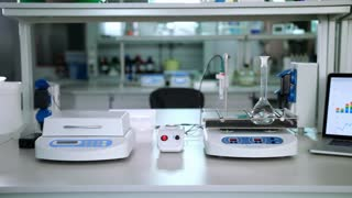 Chemistry laboratory equipment. Pure liquid mixing in glass flask at laboratory shaker. Chemical lab background. Chemical laboratory room. Chemical research equipment. Chemist working place