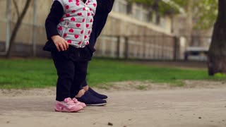 Child and parent legs walking together. Happy family child. Father with little girl. Parent and kid's feet in outdoor. Family have fun together. Joyful infant and parent walking in city park