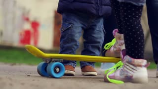 Children playing with skateboard and trying to ride. Kids legs and feet on yellow and blue skateboard. Kids having fun outdoor. Infant feet and legs learning skateboard