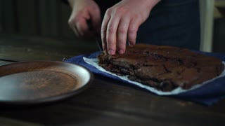 Chocolate brownie on plate. Chef serve chocolate dessert on plate. Man hands put chocolate cake pieces on ceramic plate. Serving cake. Brownie chocolate. Homemade brownie. Brownie cake