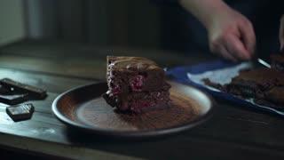 Chocolate cake pieces. Man hand put piece of chocolate cake on plate. Delicious chocolate dessert on ceramic plate. Chocolate brownie cake slices. Homemade bakery. Sweet food