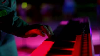 Closeup of musician playing on electronic piano at party in night club. Disco party at dance club. Piano in colored light rays. Man performing at dance party