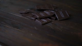 Cocoa powder in glass cup on wooden table. Dark chocolate bar. Closeup of raw dessert. Sweet ingredient for cooking cake. Chocolate chunks. Black chocolate stack. Delicious dessert. Sweet food