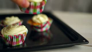 Cooking cupcakes. Hand put cup cake on baking tray. Homemade cupcakes with butter cream and coconut. Baking cupcakes. Sweet cakes. Sweet dessert