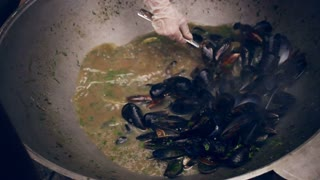Cooking mussels in pan. Mussel shells cooked in pan at street food festival. Cooking seafood on pan. Cook take mussel meal with spoon. Closeup of cooking mussels in sauce. Cooking seashells outdoor